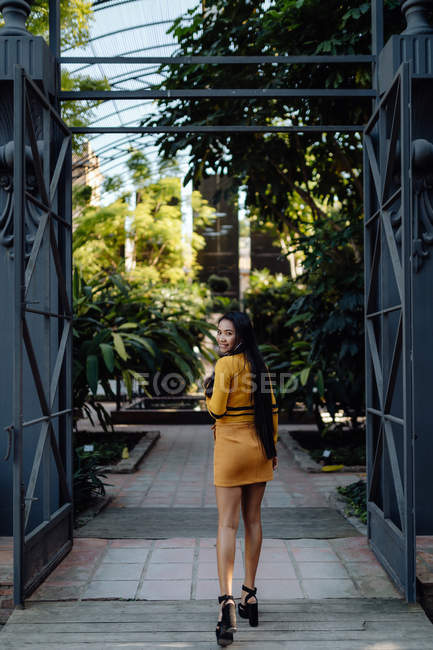 Back view of fashion trendy Asian woman walking along metal decorative fence and looking at camera over shoulder — Stock Photo