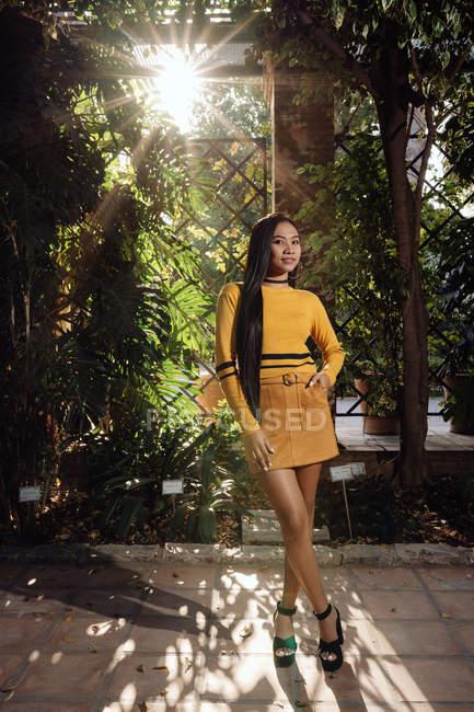 Vista laterale della donna asiatica con lunghi capelli scuri in camicia gialla e gonna corta in piedi nel bellissimo giardino e guardando la fotocamera — Foto stock
