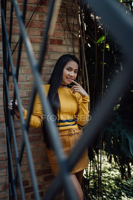 Asian woman with long hair leaning on bricked wall holding metal fence and touching lips while mysteriously looking at camera — Stock Photo