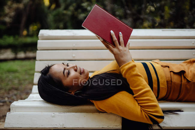 From above of brunette Asian woman reading book in red cover lying down on white bench in park — Stock Photo
