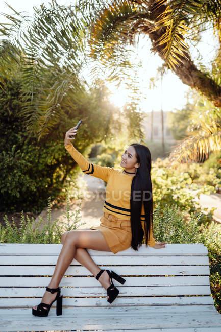 Вид сбоку на стильную брюнетку азиатской внешности со смартфоном, сидящую на задней белой скамейке — стоковое фото