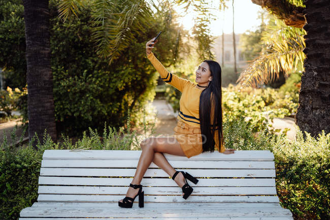 Side view of stylish brunette Asian woman with smartphone sitting on back of white bench — Stock Photo