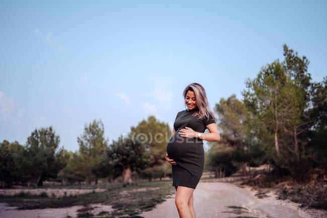 Счастливая беременная женщина в повседневной одежде гладит живот, стоя на дорожке в парке с зелеными деревьями — стоковое фото