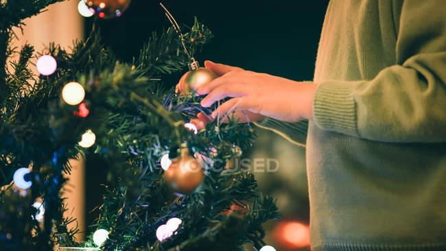 Image recadrée de Garçon décoration arbre de Noël en soirée — Photo de stock