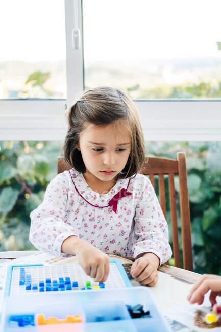 Adorable niña concentrada poniendo pequeños bloques de colores para abordar y crear mosaico mientras juega juego educativo - foto de stock