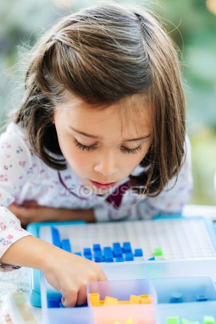 Adorabile concentrata bambina mettendo piccoli blocchi colorati a bordo e la creazione di mosaico durante il gioco educativo — Foto stock