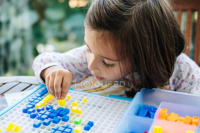 Adorável menina concentrada colocando pequenos blocos coloridos para embarcar e criar mosaico enquanto joga jogo educativo — Fotografia de Stock