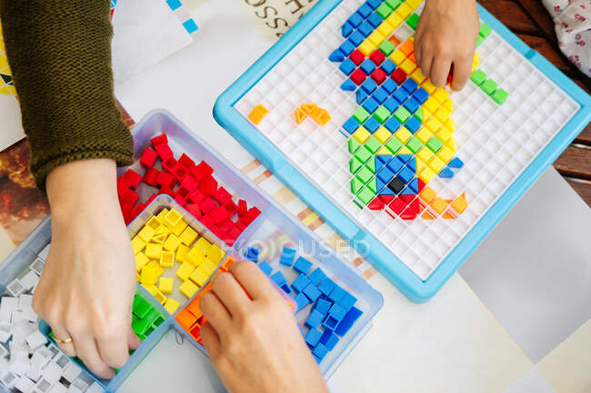 Hands over blue transparent box organizer with small colorful plastic mosaic pieces for children educational board game with empty section — Stock Photo