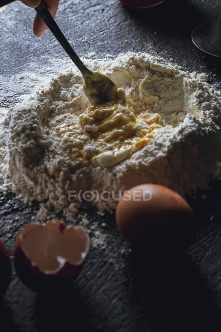 Main de la personne avec la fourchette mélanger les œufs et la farine pendant la préparation de la pâte pour les pâtes sur la table noire — Photo de stock