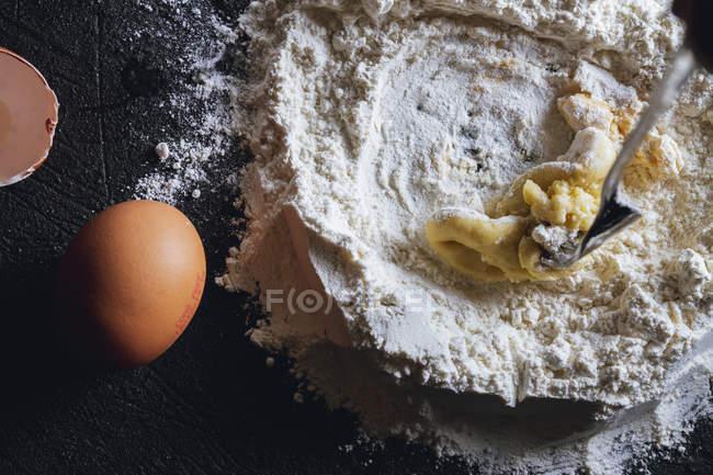 Close-up de mistura de ovo e farinha enquanto prepara massa para massas na mesa preta — Fotografia de Stock