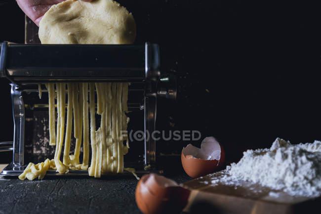 Gros plan d'une personne qui fait rouler de la pâte à la main dans une machine à pâtes tout en préparant des pâtes fraîches faites maison sur une table — Photo de stock