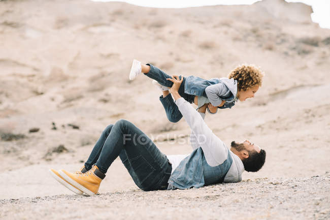 Веселый стильный этнический мужчина, лежащий, держа кудрявого счастливого малыша на песчаных горках днем — стоковое фото