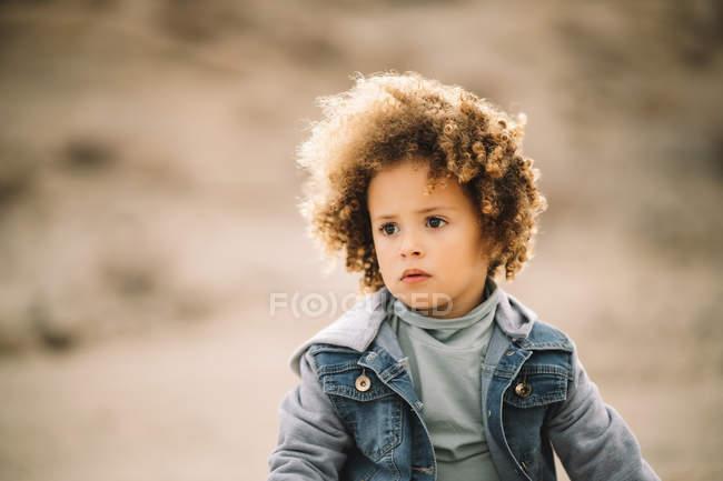 Entzückend lässig lockiges ethnisches Kind, das auf verschwommenem Hintergrund nachdenklich wegschaut — Stockfoto