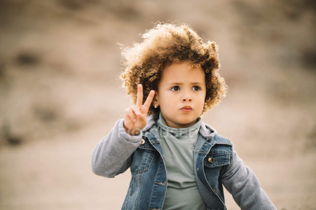 Adorable casual curly ethnic child thoughtfully looking away and making peace sign on blurred background — Stock Photo