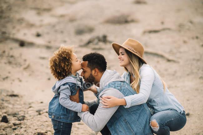 Fröhliche multirassische Eltern mit lächelnden entzückenden lockigen ethnischen Kleinkind und Spaß an sandiger Landschaft — Stockfoto