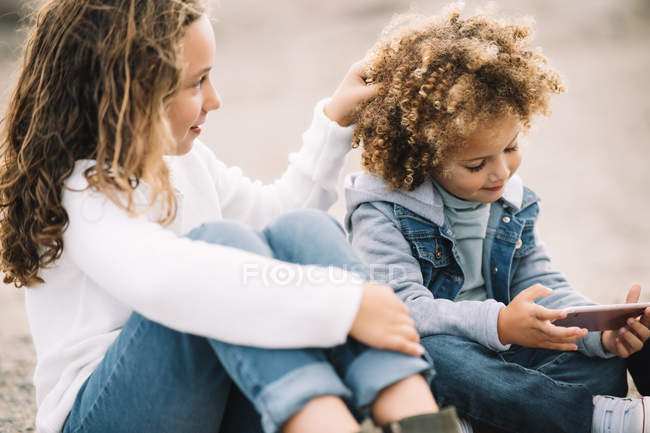 Concentrated casual mixed race kids relaxing on sand and sharing mobile phone at daytime — Stock Photo