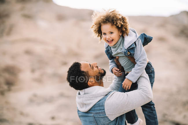 Cheerful bearded man in stylish clothes holding playing as carrying happy ethnic toddler in desert at daytime — Stock Photo