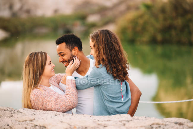 Happy casual multiracial parents together with daughter in nature — Stock Photo