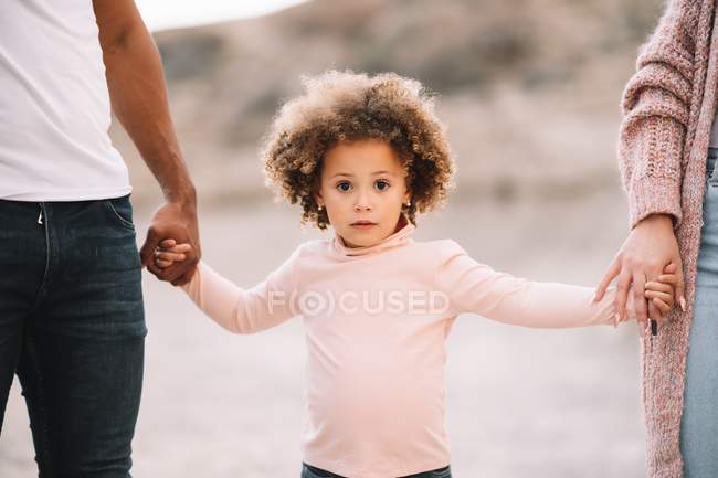 Mutter und Vater halten Händchen mit lockigem Kind beim Spazierengehen in der Natur am Tag — Stockfoto