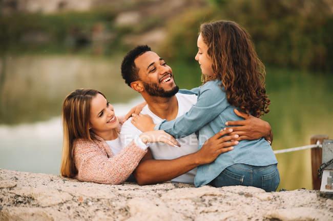 Feliz casual pais multiraciais, juntamente com filha na natureza — Fotografia de Stock