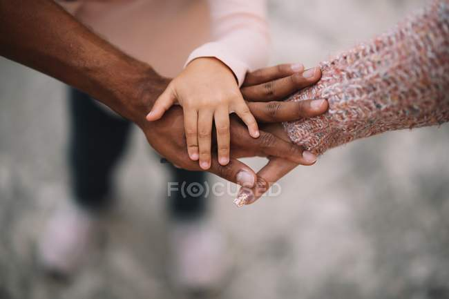Close-up of diverse parents and child joining hands together outdoors at daytime — Stock Photo