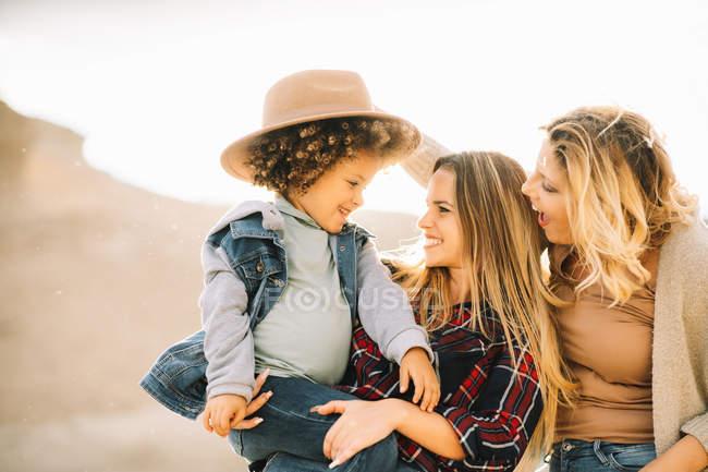 Allegro madre in camicia a scacchi che tiene bambino casuale come gioiosa amica femminile mettere cappello sul bambino sulla natura durante il giorno — Foto stock