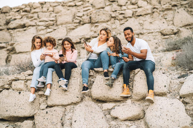 Black man, children and women using gadgets while sitting on stone wall at daytime — Stock Photo