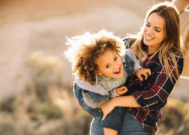Радостная блондинка держит и обнимает счастливого ребенка с кудрявыми волосами, глядя в камеру днем — стоковое фото