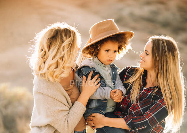 Cheerful women with cute casual toddler with curly hair resting in nature at daytime — Stock Photo