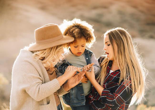 Mulheres alegres com bonito bebê casual com cabelos cacheados descansando na natureza durante o dia — Fotografia de Stock