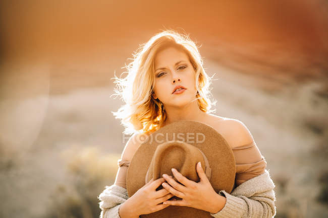 Portrait of graceful female with blonde hair holding hat in nature in backlit sunlight — Stock Photo