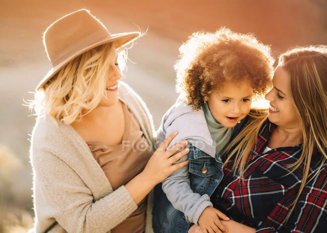 Весёлые женщины с милым случайным малышом с вьющимися волосами, отдыхающие днем на природе — стоковое фото