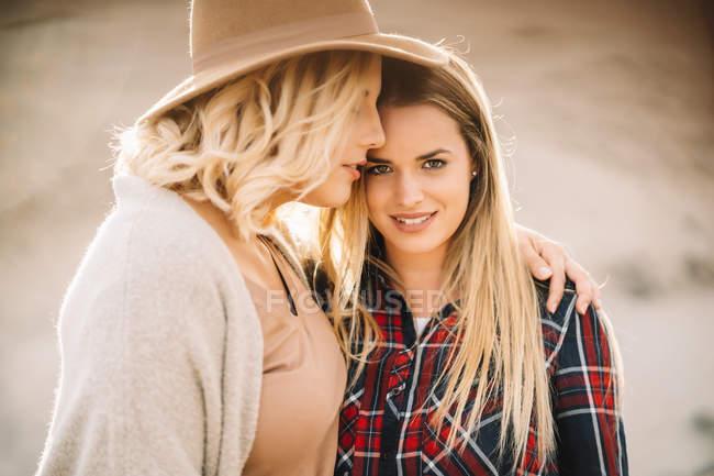 Frau mit Hut zärtlich umarmt Frau mit langen Haaren gekleidet in kariertem Hemd schaut in die Kamera auf die Natur — Stockfoto
