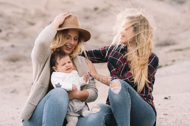 Счастливая женщина в шляпе сидит на песке и держит ребенка, в то время как подруга поддерживает их в ветреную погоду в дневное время — стоковое фото