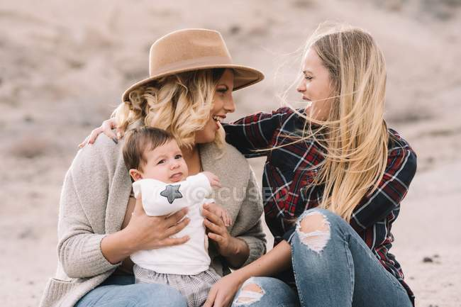 Happy woman in hat sitting on sand and holding baby while female friend supporting them in windy weather at daytime — Stock Photo