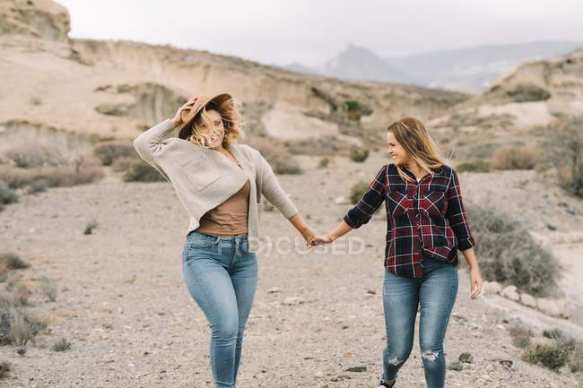 Frau mit Hut hält zärtlich Händchen mit Freundin im karierten Hemd und lächelt, als ginge sie in der Natur — Stockfoto