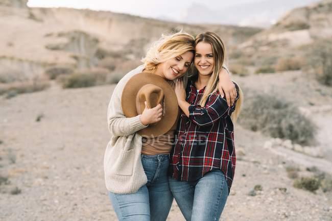 Frau mit Hut zärtlich umarmt Frau mit langen Haaren sieht in die Kamera gekleidet in kariertem Hemd lächelnd auf die Natur — Stockfoto