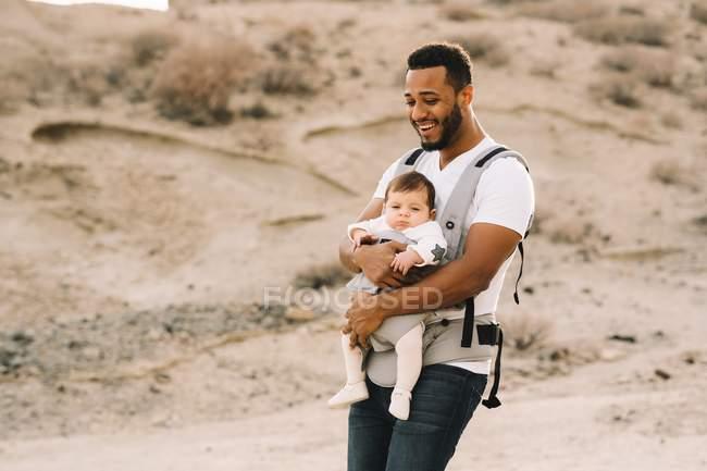 Homme afro-américain gai et barbu portant un t-shirt blanc et des jeans tenant son bébé dans son porte-bébé tout en se promenant dans la nature — Photo de stock