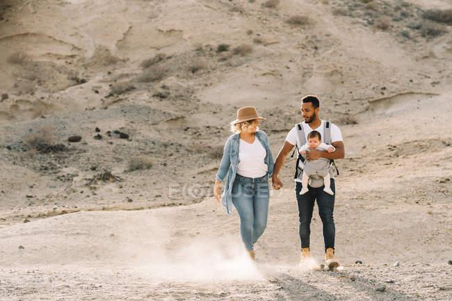 Hombre alegre que lleva un bebé pequeño y que lleva las manos con la esposa rubia mientras camina en el desierto arenoso. - foto de stock
