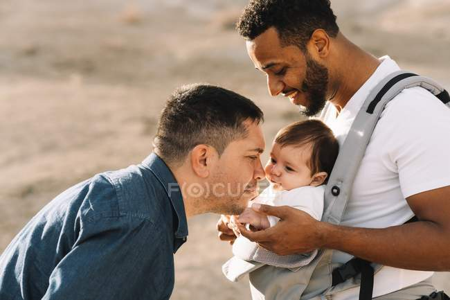 Multiracial fathers cuddling and kissing little baby outdoors — Stock Photo