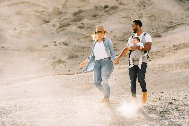 Cheerful man carrying little baby and holding hands with blonde wife while walking in sandy desert — Stock Photo