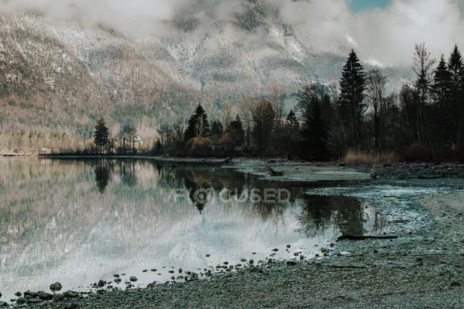 Paesaggio pittoresco di tranquillo lago trasparente circondato da montagne innevate e foresta oscura a Hallstatt — Foto stock
