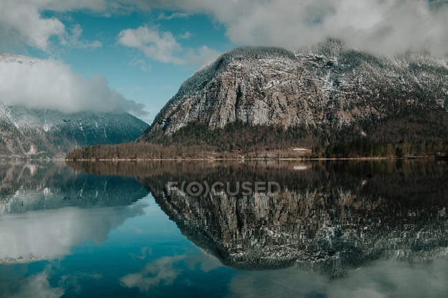 Serene stunning landscape of motionless lake reflecting bright cloudy sky surrounded by snowy mountains in Hallstatt — Stock Photo