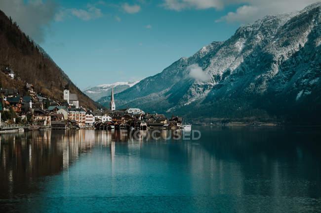 Esplendido paisaje de pintoresca costa con edificios y montañas a lo largo de un tranquilo lago de cristal que refleja cielo y nubes en Hallstatt. - foto de stock