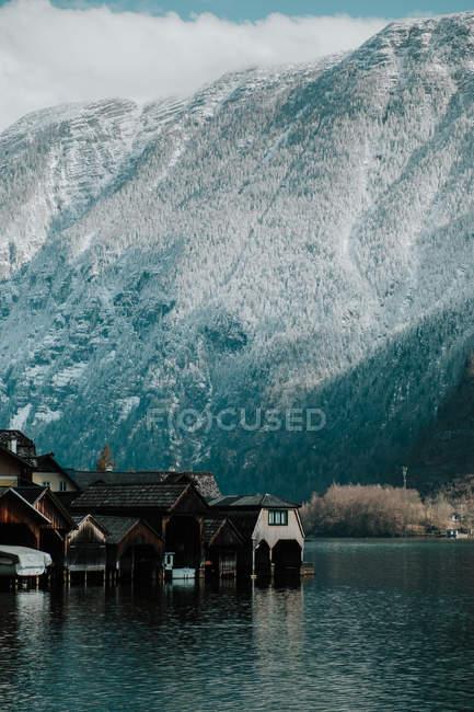 Traumhafte landschaft aus hölzernen pfahlhäusern in ruhigem wasser umgeben von schneebedeckten felsigen bergen in hallstatt — Stockfoto