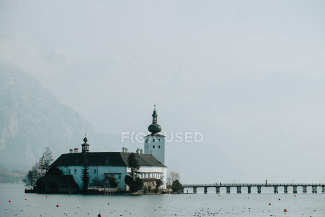 Calm landscape of white small church in gray water surrounded by snowy rocky mountains in Salzburg — Stock Photo