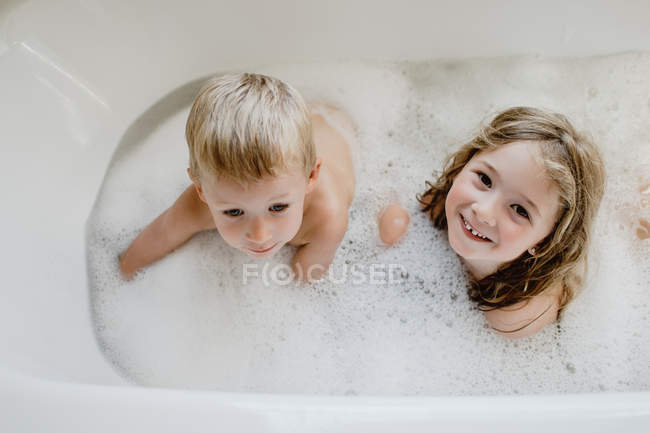Funny children playing with foam in bath — Stock Photo