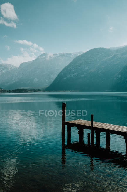 Serene landscape on empty wooden pier in crystal calm water reflecting sky and snowy mountains in bright daytime in Hallstatt — Stock Photo