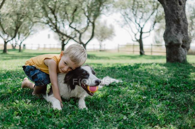 Entzückendes Kind liegt und umarmt Fleck flauschigen Hund mit Ball im Mund in Graswiese im Park — Stockfoto