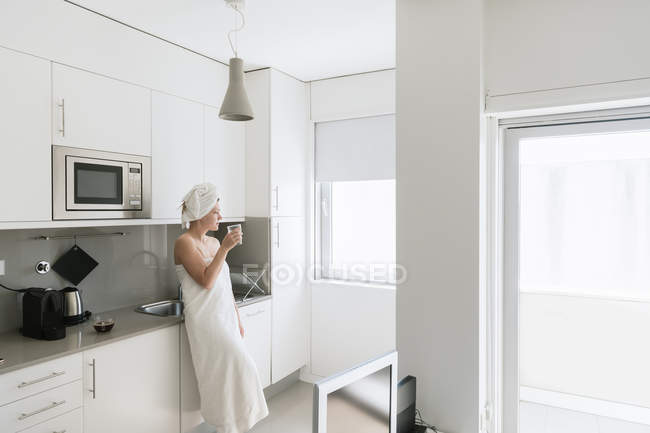 Pensive woman having refreshment with water in comfortable kitchen — Stock Photo